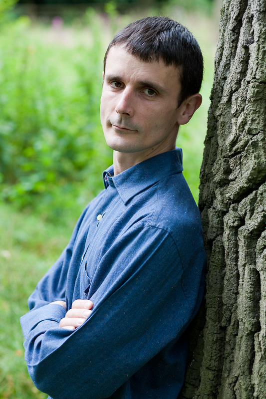 Tristan Titeux in blue shirt standing by a tree