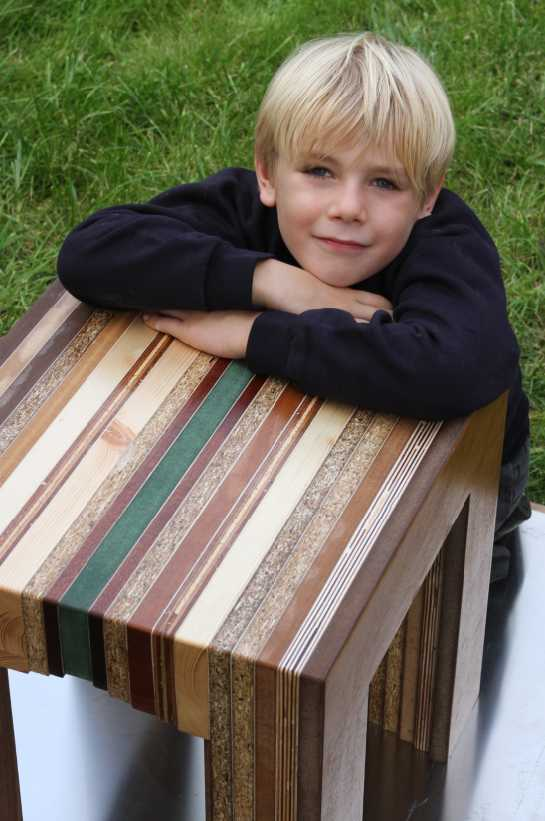 boy leaning on colourfull stripy table