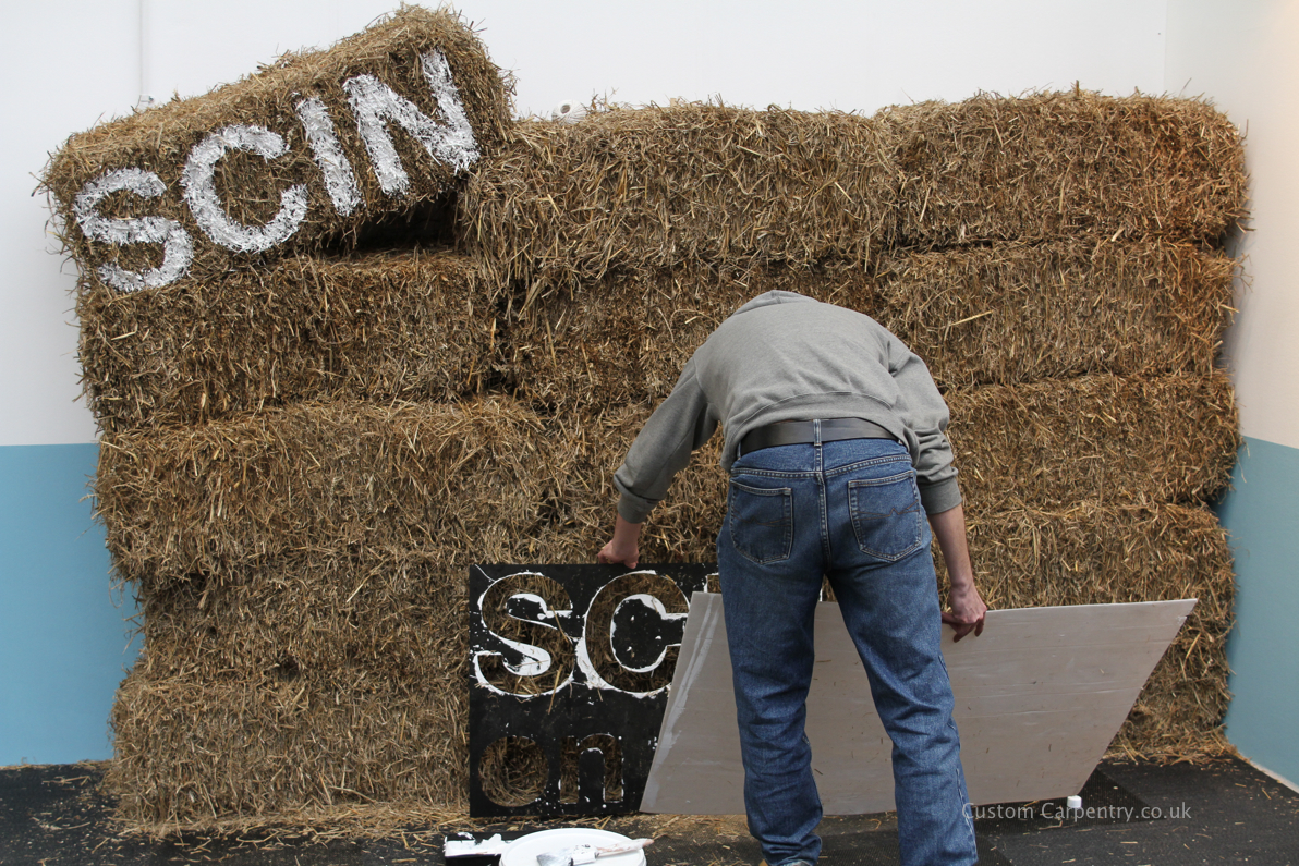Man painting writting on a wall of straw bales